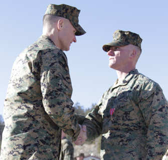 Gunnery Sgt. Matthew Nagel shakes hands with Col. Phillip Chandler, the commanding officer of Marine Corps Mountain Warfare Training Center Bridgeport, after receiving a Bronze Star Medal for meritorious achievement and combat service in Afghanistan, during an award ceremony Feb. 1, 2011, at the Center's command post.