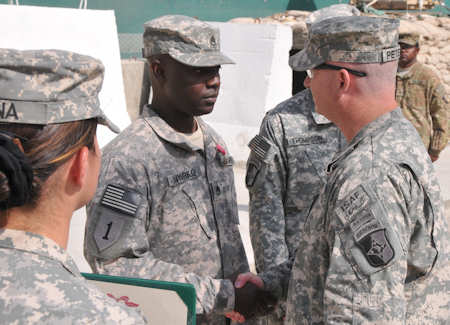 Col. Michael Peterman, 101st Sustainment Brigade commander, shakes hands with Staff Sgt. Kofi Nyarko, 101st Sustainment Brigade Support Operations, after he receives his Bronze Star Medal at the unit's End of Tour Awards Ceremony on Oct. 9, 2011. Photo by Army Sgt. 1st Class Peter Mayes