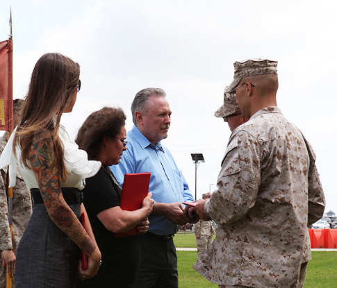 Staff Sgt. Jeremy Smith's father, Jerry Smith, receives a Bronze Star Medal on his behalf from Maj. Mark Wood, the commanding officer of Alpha Company, 1st Battalion, 23rd Marine Regiment at Ellington Field Joint Armed Forces Reserve Center, April 14, 2012. Smith was posthumously awarded the Bronze Star for heroic actions during a tour in Afghanistan in support of Operation Enduring Freedom. Photo by USMC Lance Cpl. Jessica DeRose