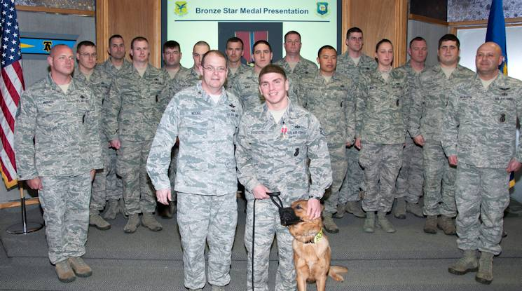 U.S. Air Force Staff Sgt. Jason Spangenberg, 436th Security Forces Squadron dog handler, poses with Col. Rick Moore, 436th Airlift Wing commander, his dog, Rico, and members of his unit after receiving the Bronze Star Medal March 4, 2014, at Dover Air Force Base, Del. Spangenberg supported Army Special Operations forces in more than 100 combat mission during his deployment. (U.S. Air Force photo by Senior Airman Jared Duhon)