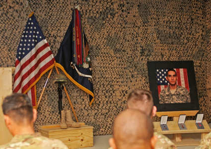 A memorial display and photo of U.S. Army Pfc. Jonathan Villanueva stand before an audience of 4th Brigade Combat Team, 10th Mountain Division's Task Force Patriot soldiers and civilians attending a memorial service for Villanueva on Combat Outpost Sultan Khel in Wardak province, Afghanistan, May 6, 2011. Villanueva was a 19-year-old soldier from Jacksonville, Fla., assigned to 4th Platoon, Company D, 2nd Battalion, 4th Infantry Regiment's Task Force Warrior when he died as a result of wounds he suffered from small-arms fire during an enemy engagement in Wardak, April 27, 2011. Photo by U.S. Army Sgt. 1st Class Matt Meadows