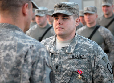 Army 1st Lt. Richard Warehime is pinned with the Bronze Star Medal, which is given for bravery, acts of merit, or meritorious service, just minutes before his team departs on its next route clearance mission in Baghdad, February 2009.