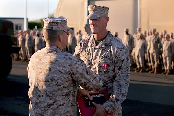 First Sgt. William Pinkerton IV, the Headquarters Battery first sergeant of 1st Battalion, 12th Marine Regiment, shakes hands with Lt. Col. Michael Roach, commanding officer of 1st Bn., 12th Marines during Pinkerton's Bronze Star Medal with Combat V ceremony, March 15, 2013. Pinkerton received a Bronze Star Medal with Combat V for his efforts supporting Operation Enduring Freedom in Afghanistan in 2010. (U.S. Marine Corps photo by Lance Cpl. Nathan Knapke)