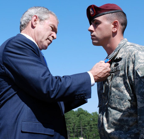 Sgt. Christopher Corriveau, Headquarters and Headquarters Company, 2nd Battalion, 505th Parachute Infantry Regiment, 3rd Brigade Combat Team, 82nd Airborne Division, is awarded the Distinguished Service Cross from President George W. Bush on May 22, 2008 during the Division's Review at Fort Bragg, N.C. Corriveau, a native of Lewiston, Maine, is credited with repelling an overwhelming and heavily-armed force Aug. 26, 2007. His four man sniper team courageously fought off an enemy force in close combat for control of a rooftop during Operation Iraqi Freedom killing or wounding at least 10 insurgents.