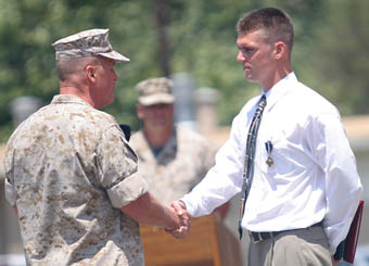 Lt. Gen. John F. Sattler, commanding general of the I Marine Expeditionary Force, congratulates former Marine Sgt. Robert J. Mitchell on his receipt of the Navy Cross during a ceremony aboard Camp Pendleton, Calif., July 28, 2006.  Mitchell who was wounded four times during his two tours in Iraq, received the medal, the nation's second-highest award for battlefield heroism, in recognition of his actions during the battle for Fallujah, Iraq in November 2004.