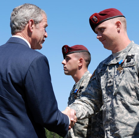 Sgt. Eric Moser (right), Charlie Company, 2nd Battalion, 505th Parachute Infantry Regiment, 3rd Brigade Combat Team, 82nd Airborne Division, is awarded the Distinguished Service Cross by President George W. Bush on May 22, 2008 during the Division's Review at Fort Bragg, N.C. Moser, a native of Houston, is credited with repelling an overwhelming and heavily-armed force Aug. 26, 2007. His four man sniper team courageously fought off an enemy force in close combat for control of a rooftop during Operation Iraqi Freedom killing or wounding at least 10 insurgents.