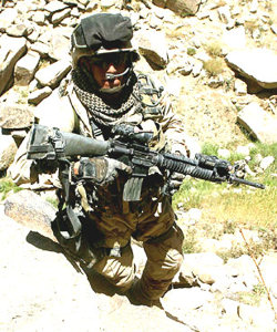 With bloodstains visible on the lower portion of his left trouser leg, Marine Sgt. Anthony Viggiani pauses to look at the camera moments after a fierce firefight with anti-coalition militia in central Afghanistan. Viggiani, a squad leader in Company C, Battalion Landing Team, 1st Battalion, 6th Marines, ignored the bullet wound to remain in the fight against the enemy. U.S. Marine Corps photo by Gunnery Sgt. Keith A. Milks