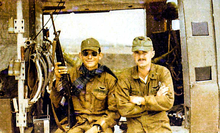 "Warrant Officer Danne Smith, U.S. Army UH-1H helicopter pilot,(right) with a friend in the door to his UH-1H helicopter in Vietnam in the early 1970s. The war veteran survived being shot down six times and received three Air Medals with ""V"" devices, three Bronze Stars and two Silver Stars during his tour in Vietnam.(Courtesy photo by Danne Smith)"