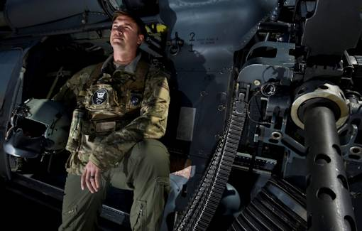 U.S. Air Force Staff Sgt. Justin Tite, 88th Test and Evaluation Squadron aerial gunner, poses next to an M2 .50 caliber machinegun on a HH-60 Pave Hawk April 4, 2012 at Nellis Air Force Base, Nev. Tite was awarded the Distinguished Flying Cross for engaging the enemy during a six-hour-long sortie which resulted in the life-saving rescue of two soldiers and recovery of another from the battlefield. U.S. Air Force photo by Airman 1st Class Daniel Hughes