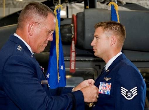 U.S. Air Force Maj. Gen. Bill Hyatt, U.S. Air Force Warfare Center commander, presents the Distinguished Flying Cross with Valor to Staff Sgt. Justin Tite, 88th Test and Evaluation Squadron aerial gunner, July 9, 2012, at Nellis Air Force Base, Nev. Tite received the prestigious medal for life saving combat operations in Afghanistan where he identified and eliminated enemy combatants, enabling the rescue of injured soldiers. U.S. Air Force photo by Staff Sgt. William P. Coleman