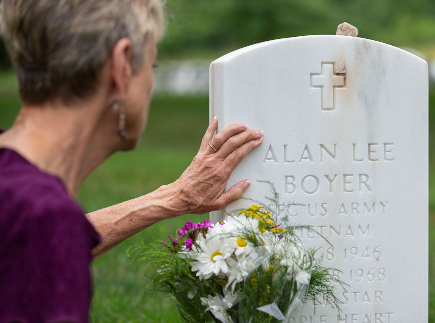 Judi Boyer-Bouchard touches the headstone for her brother, Sgt. 1st Class Alan Boyer, during a visit to Arlington National Cemetery, VA on June 20, 2018. (U.S. Army photo by Sean Kimmons)