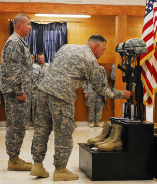 "Col. Paul T. Calvert, right, commander of 2nd ""Dagger"" Advise and Assist Brigade, 1st Infantry Division, United States Division – Center and Command Sgt. Maj. Rodney R. Lewis, left, senior enlisted advisor of 2nd AAB, 1st Infantry Division, pay their respects at the fallen soldier battle crosses of Sgt. 1st Class Clifford Beattie and Pfc. Ramon Mora Jr. May 26, 2011 at Camp Liberty, Iraq. Beattie, 37, a Tempe, Ariz., native, and Mora, 19, a Covina, Calif., native, both of Headquarters and Headquarters Company, 1st Battalion, 63rd Armor Regiment, died May 22, 2011 of wounds suffered when enemy forces attacked their unit with an improvised explosive device. Photo by Army Sgt. Daniel Stoutamire"