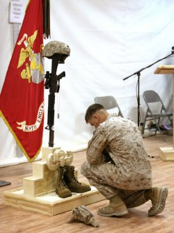 A Marine pays his final respects to Gunnery Sgt. Christopher Eastman  during a memorial service at Camp Leatherneck, Afghanistan, July 25, 2010. Photo by Royal Air Force Cpl. Patricia Morrison