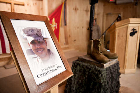 A photograph of Staff Sgt. Christopher Diaz alongside his monument during a remembrance ceremony at Camp Leatherneck chapel on Oct. 8, 2011. Diaz, a native of El Paso, Texas, and an expert military working dog handler with II Marine Expeditionary Force Headquarters Group (Forward), Task Force Belleau Wood, died Sept. 28, 2011, while supporting combat operations in Helmand province. Diaz was deployed out of Marine Corps Air-Ground Combat Center Twentynine Palms, Calif., where he served as a handler with III MHG. Navy Photo by Petty Officer 2nd Class Jonathan Chandler
