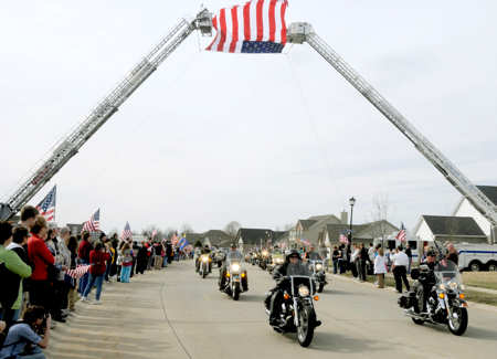 Patriot Guard Riders lead the funeral procession route of Airman 1st Class Zachary Cuddeback March 12, 2011, in O'Fallon, Ill. Airman Cuddeback and another Airman were killed March 2, 2011, when a man opened fire on a bus carrying U.S. Airmen at an airport in Frankfurt, Germany. Airman Cuddeback will be laid to rest next to his grandfather at a cemetery in O'Fallon, Ill. U.S. Air Force photo byStaff Sgt. Brian J. Valencia