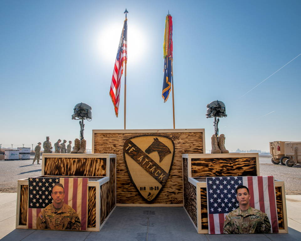 November 22, 2019 - Battle cross displays honor fallen Chief Warrant Officer 2 David C. Knadle and Chief Warrant Officer 2 Kirk T. Fuchigami Jr. in Erbil, Iraq with fellow troopers with the U.S. Army 1st Attack Reconnaissance Battalion, 227th Aviation Regiment and 244th Combat Aviation Brigade's Task Force Warhawk saluting off scene during their memorial service. The Apache helicopter pilots were killed when their helicopter crashed while providing security to ground troops in Logar Province, Afghanistan on November 20, 2019. (Image created by USA Patriotism! from U.S. Army photo by Staff Sgt. Joshua Hammock)