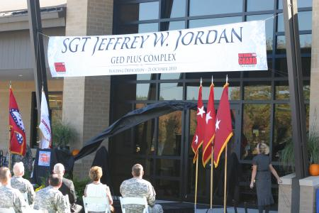 Ms. Lacey Jordan unveils the new building sign bearing the name of her late husband Sgt. Jeffrey W. Jordan, Oct. 21, 2010 at Camp Robinson In North Little Rock, Ark. U.S. Army Photo by Spc. Tyson Shields