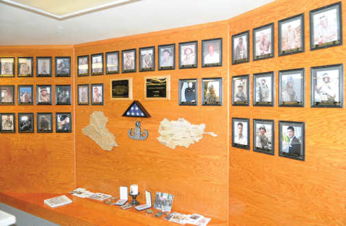 "A memorial tribute that shows 35 explosive ordnance disposal Marines who have died supporting operations in Iraq and Afghanistan, and on duty, stands at the Combined Explosive Ordnance Disposal Unit building at the Marine Corps Air Station in Yuma, Ariz., March 1, 2011. ""Every EOD tech on this wall we know, either personally or we've worked with them,"" said Chief Warrant Officer 2 Simon Wade, unit officer in charge. ""There's a story behind every one of these guys."" When the wall was first dedicated, it was a simple one-faced structure that only had 19 faces on it, and wood cutouts of Iraq and Afghanistan. The wall has since expanded in commemorating the deceased, the country models far more detailed with the locations of major cities and rivers etched into them, courtesy of Marine Wing Support Squadron 371 combat engineers."
