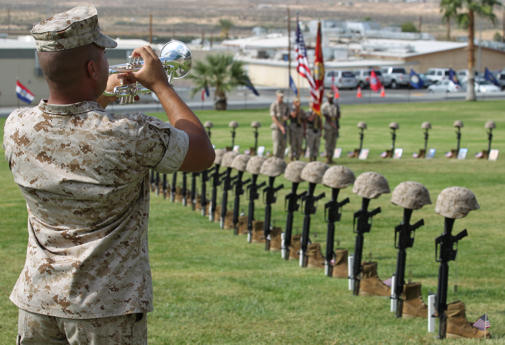 A trumpet player in the Combat Center's Band plays taps over the 74 memorial crosses during Regimental Combat Team 7's memorial ceremony Oct. 15, 2010 at Lance Cpl. Torrey L. Gray Field. RCT-7 was deployed to Afghanistan from Oct. 24, 2009 to Sept. 28, 2010.