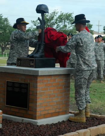 "Lt. Col. Nathan Cook, the commander of 3rd Battalion, 82nd Field Artillery Regiment, 2nd Brigade Combat Team, 1st Cavalry Division, and Command Sgt. Maj. Carlos SotoBonilla, the ""Red Dragons"" Command Sgt. Maj., unveil a new memorial on Fort Hood, Texas, Sept. 10, 2010 dedicated to the six soldiers the unit has lost during its three rotations to Iraq in support of Operation Iraqi Freedom."