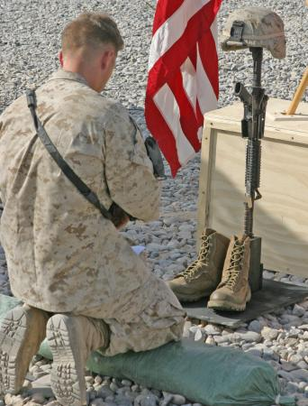 A Marine with 2nd Battalion, 9th Marine Regiment, pays his respects to Petty Officer 3rd Class James M. Swink II, a hospital corpsman with Golf Company, 2/9, during a memorial service at Combat Outpost Reilly, Marjah, Afghanistan, Aug. 31. Swink was killed, Aug. 27, while conducting combat operations in Helmand province, Afghanistan.