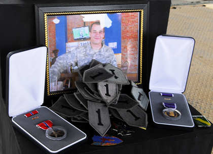First Infantry Division shoulder sleeve insignia – former wartime service (center) and awards and decorations cover the memorial stand, Jan. 19, at a service at Joint Security Station Loyalty, Iraq, honoring the life of Spc. Jose Torre, Jr. (pictured), formerly with Company C, Special Troops Battalion, 2nd Advise and Assist Brigade, 1st Inf. Div., United States Division – Center. Torre died, Jan. 15, 2011 in Baghdad of wounds suffered when insurgents attacked his unit.