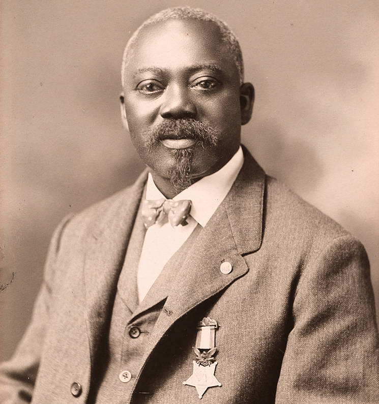 The Medal of Honor was awarded to U.S. Army Sgt. William H. Carney, Company C, 54th Massachusetts Colored Infantry Regiment, for Gallantry at Fort Wagner, S.C., July 18, 1863 ... and issued in 1900. (Gelatin silver print of William Harvey Carney between 1901 and 1908 ... which is public domain in the U.S. since it was published in the U.S. before 1923.)