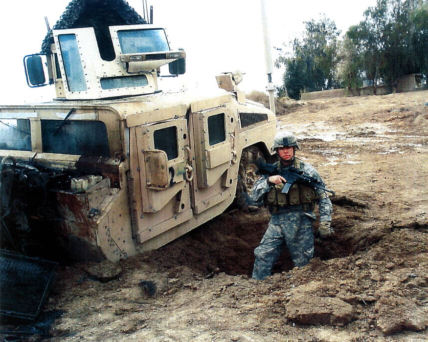 Staff Sgt. Travis Atkins stands next to his vehicle after it was damaged by an improvised explosive devise in Iraq during 2007. (U.S. Army courtesy photo)