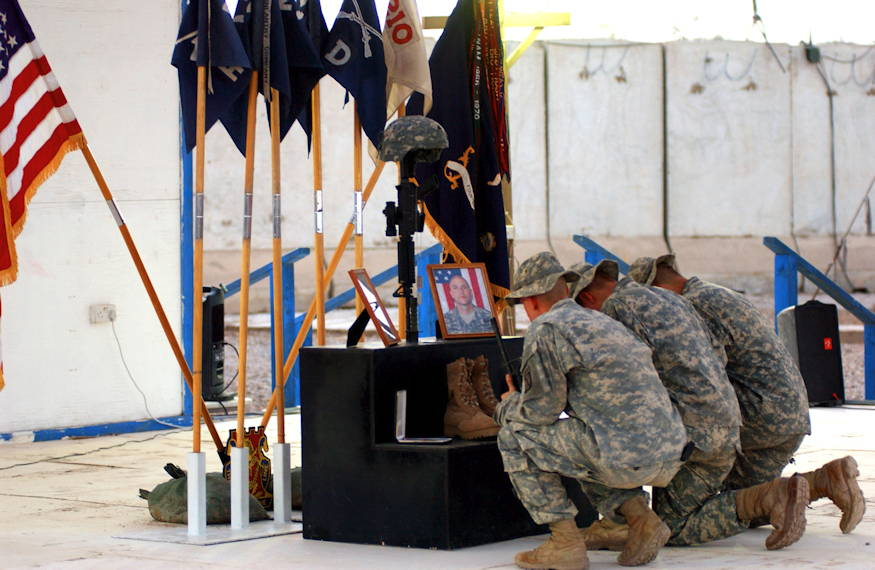 Soldiers kneel to pay their respects to Staff Sgt. Travis Atkins, who was killed, June 1, 2007, by a suicide bomber near Sadr Al-Yusufiyah, Iraq, at a memorial ceremony held, June 7, 2007 at Camp Striker. Atkins was on a patrol with his unit, Company D, 2nd Battalion, 14th Infantry Regiment, 2nd Brigade Combat Team, 10th Mountain Division (Light Infantry) from Fort Drum, New York, when they detained men who were wearing suicide vests. (U.S. Army photo by Spc. Chris McCann)