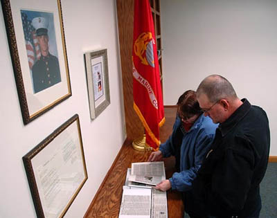 Parents Deb and Dan Dunham look at press clippings in town's library room dedicated to their son in Scio, NY.