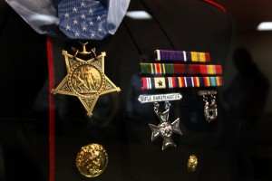 Cpl. Jason Dunham's Dress Blues hang in the captain's mess of the vessel bearing his name, along with his ribbon rack and the Medal of Honor draped around the shoulders.