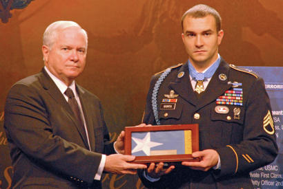 "Secretary of Defense Robert M. Gates presents Staff Sgt. Salvatore ""Sal"" Giunta with a Medal of Honor flag during a Hall of Heroes ceremony at the Pentagon Nov. 17, 2010."