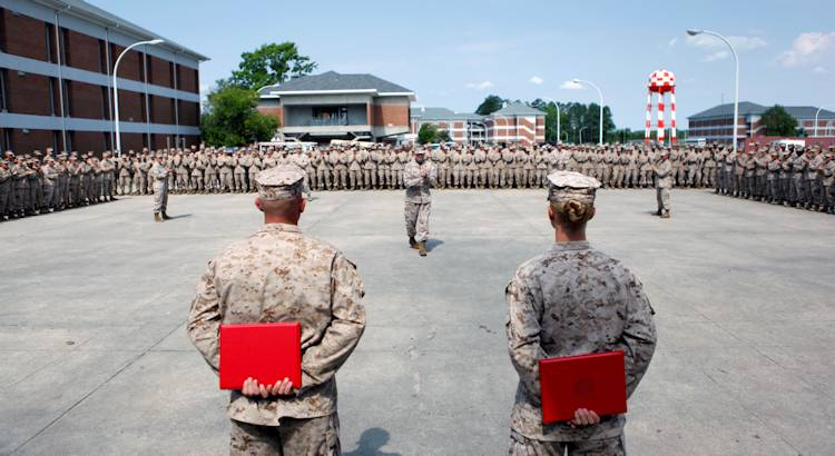 Sgt. Kirby D. Kuhn and Sgt. William P. Goodacre, combat instructors with Company F, Combat Training Battalion, School of Infantry - East, receive applause from their chain of command, fellow combat instructors and students after receiving Navy and Marine Corps Achievement Medals during an awards ceremony aboard Camp Geiger, a satellite base of Marine Corps Base Camp Lejeune, N.C., June 17. Kuhn and Goodacre used their training to get a Marine who started seizing to breathe again. Their efforts saved her life during a M203 grenade launcher practical application exam, May 26, 2013. (U.S. Marine Corps photo by Cpl. Charles Clark)