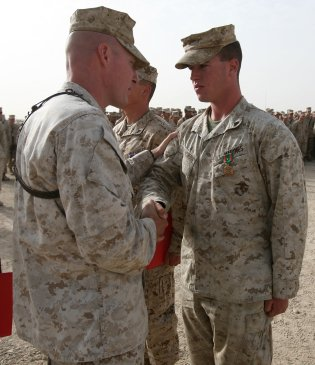 CAMP LEATHERNECK, Afghanistan-Corporal Rory MacEachern, a military policeman with Combat Logistics Battalion 6, 1st Marine Logistics Group (Forward), is congratulated by his commanding officer, Maj. William Stophel, upon being awarded the Navy and Marine Corps Achievement Medal with Combat Distinguishing Device here, July 30, 2010. During combat logistics patrols ranging from March through May, the North Attleboro, Mass., native, distinguished himself through superior performance of his duties as a machine gunner. On more than one occasion MacEachern was able to effectively eliminate enemy threats with precision fire from his position as a gunner, allowing each combat logistics patrol to continue safely.