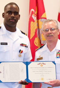 U.S. Navy Ensign Sean Barner holding his Navy and Marine Corps Medal certificate with U.S. Navy Captain Steve Kirby on June 14, 2011.