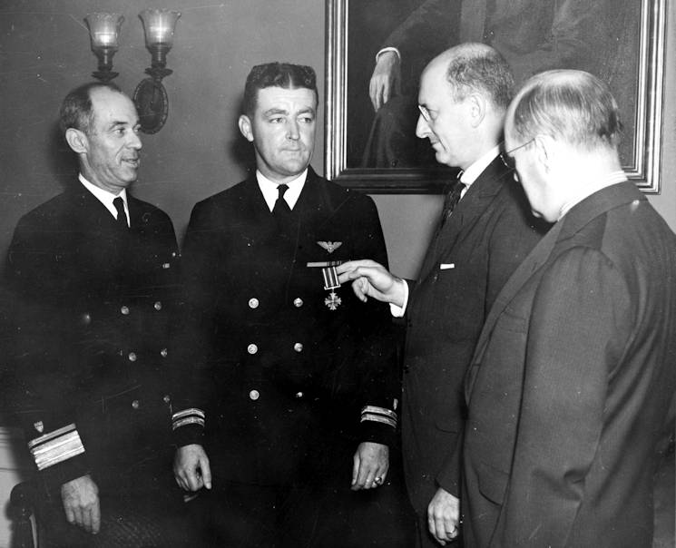 Coast Guard Lt. Burke receives his first Distinguished Flying Cross from Treasury Secretary Henry Morgenthau, Jr. On the left stands Coast Guard Commandant Russell R. Waesche. (U.S. Coast Guard photo)