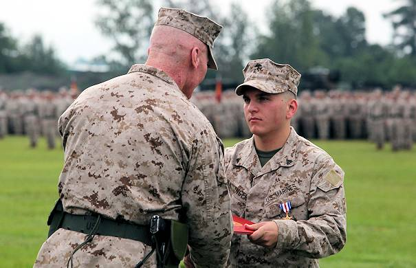 Philadelphia native Cpl. Jason M. Hassinger (center right), receives the Silver Star from Maj. Gen. John A. Toolan, the outgoing commanding general of 2nd Marine Division during the 2nd Marine Division change-of-command ceremony Aug. 23, 2012 aboard Camp Lejeune. Hassinger received the Silver Star for his actions during an ambushed patrol in Marjah, Helmand province, Afghanistan, in which he led his section through intense fire to rescue a group of fellow Marines pinned down by the enemy. Hassinger was shot four times during the incident but continued to fight until the enemy retreated. The Silver Star is the third-highest award a U.S. service member can receive for valor in combat. Photo by USMC Cpl. Tommy Bellegarde