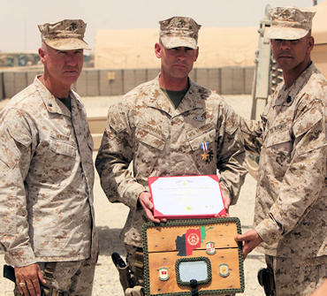 HELMAND PROVINCE, Afghanistan-Warrant Officer John Hermann (center), 32, from Tucson, Ariz., explosive ordnance disposal officer for 1st Explosive Ordnance Disposal Company, 1st Marine Logistics Group (Forward), stands with Brig. Gen. Charles L. Hudson (left), commanding general of 1st MLG (FWD), and Sgt. Maj. Antonio Vizcarrondo Jr., sergeant major of 1st MLG (FWD), after being awarded the Silver Star medal at Camp Delaram II, Helmand Province, Afghanistan, July 15, 2010. Photo by Sgt. Brandon Owen
