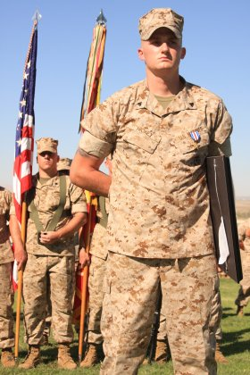 Corporal Daniel Hickey, a team leader with 2nd Battalion, 7th Marine Regiment, stands tall bearing his Silver Star and holding his award citation in front of the color guard and his battalion at Lance Cpl. Torrey Gray Field, July 16, 2010.