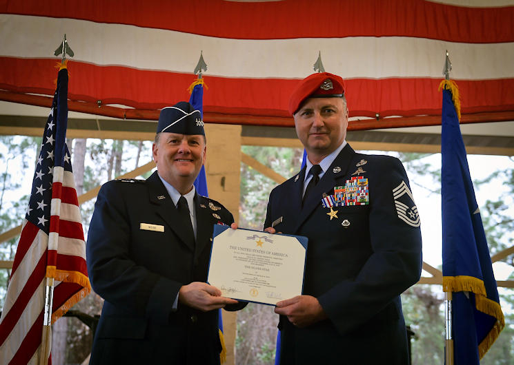 December 15, 2017 - Lt. Gen. Brad Webb, commander of Air Force Special Operations Command, presents a Silver Star Medal certificate to Chief Master Sgt. Michael West, a Special Tactics operator with the 24th Special Operations Wing, during his ceremony, , at Hurlburt Field, Florida. West was awarded the SSM for a five-day battle, dubbed Operation MEDUSA, in 2006. West utilized 58 coalition strike aircraft to deliver 24,000 pounds of precision ordnance to eliminate more than 500 enemy forces to secure the safety of 51 Special Forces soldiers and 33 coalition partners. (U.S. Air Force photo by Senior Airman Ryan Conroy)