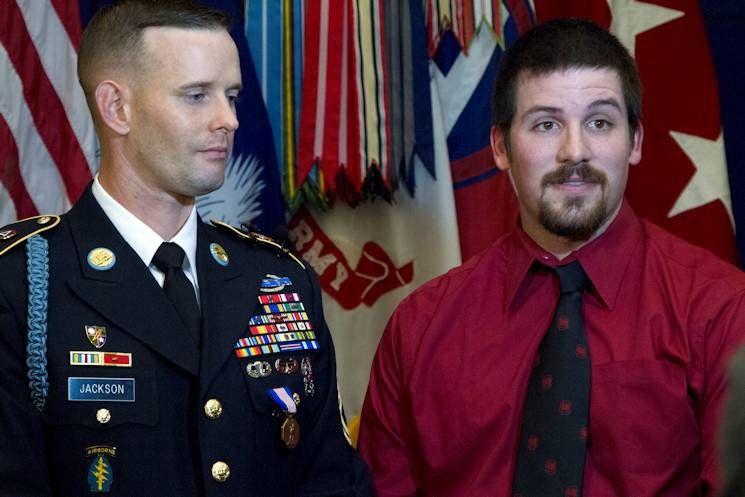 Jeremy Brunson (right) speaks to local media about the details of his traffic accident and rescue by U.S. Army Central Soldier, Sgt. 1st Class John M. Jackson, at the conclusion of a ceremony honoring the Soldier's heroism at Patton Hall, Dec. 19, 2014. Jackson received the Soldier's Medal at an event which included USARCENT leadership and South Carolina state leaders, in addition to an audience of fellow service members, Department of the Army civilians and family members. (U.S. Army photo by Sgt. Sharmain Burch)