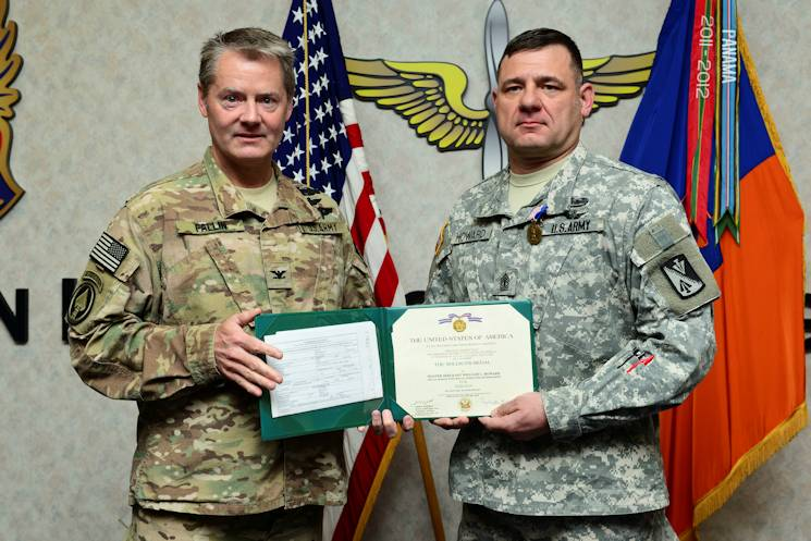 U.S. Army Col. Don Fallin, Special Mission Wing, Special Operations Join Task Force commander, left, awards 1st Sgt. William Howard, Hotel Company, 1st Battalion, 222nd Aviation Regiment, 128th Aviation Brigade first sergeant, a Soldier's Medal at Fort Eustis, Va., April 3, 2015. During Howard's sixth deployment, he helped save the lives of five Afghan soldiers after a rocket attack locked them inside of their prayer room in a hangar which had caught fire. (U.S. Air Force photo by Senior Airman Kimberly Nagle)