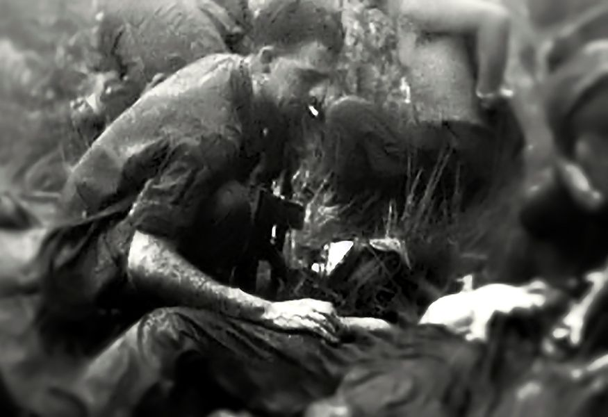 """U.S. Army Spc. Richard """"Dickie"""" Allen Cable, rifleman assigned to B Company, 1st Battalion, 16th Infantry Regiment of the 1st Infantry Division, assists a wounded soldier in Vietnam in the late 1960's. U.S. Army 1st Sgt. Richard """"Dickie"""" Allen McChesney talks about his namesake and why he serves his country. (Courtesy photo provided by U.S. Army 1st Sgt. Richard Allen McChesney)"""