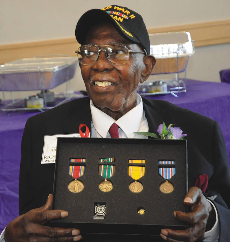 August 26, 2017 - Richard Bell, a 99-year-old veteran and Blackstone resident, poses for pictures with medals he earned more than 72 years ago in World War II during a family reunion event Aug. 26 at the Eastern Henrico Recreation Center. Bell was a participant in the Red Ball Express logistical operation during the war. Bell's great nephew and former reporter Benjamin Sessoms Jr. discovered a year ago his relative never received awards pertaining to his military service and initiated efforts for a formal presentation. Congressman Dave Brat along with Brig. Jeffrey Drushal, Chief of Transportation at Fort Lee, presented the medals. (Photo by Terrance Bell, U.S. Army Garrison Fort Lee PA)