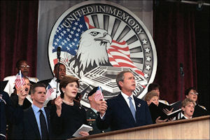 President George W. Bush and first lady Laura Bush waving the flag and singing 'God Bless America' during a memorial service at the Pentagon on Oct. 11, 2001, in honor of those who perished in the terrorist attack on the building. DoD Photo by R. D. Ward