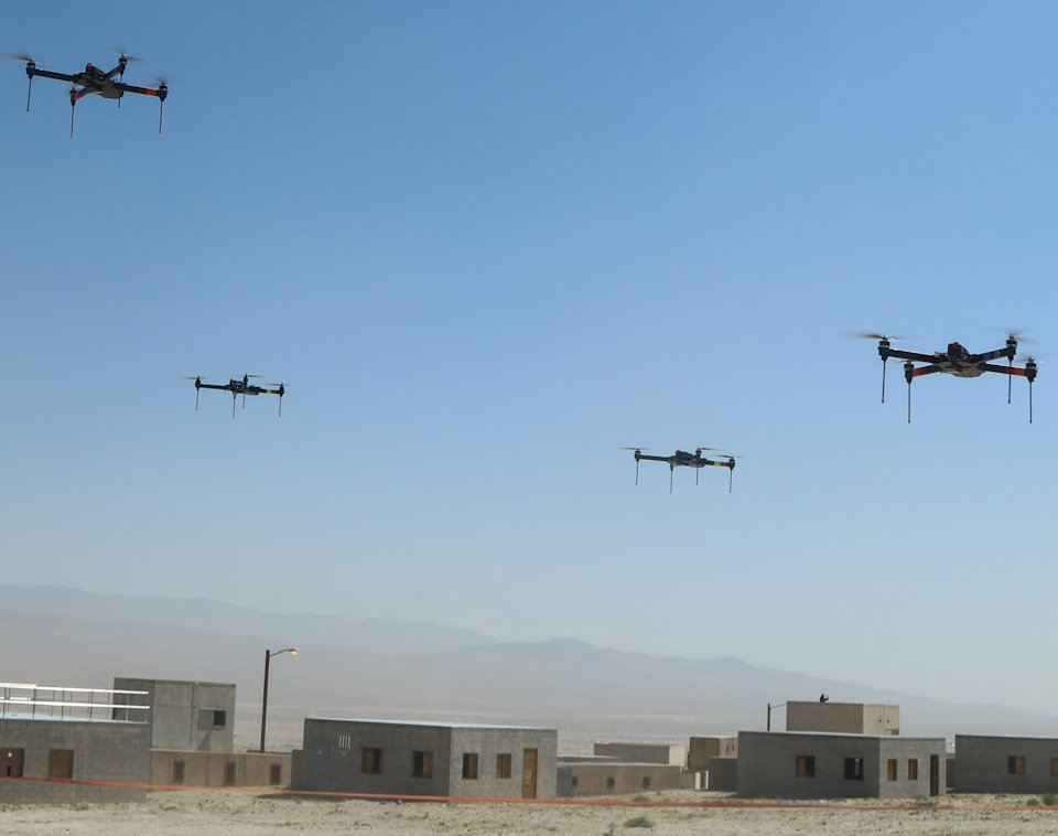 The 11th Armored Cavalry Regiment and the Threat Systems Management Office push a swarm of 40 drones through the town during the battle of Razish, National Training Center on May 8, 2019. This exercise was the first of many held at the National Training Center. (Image created by USA Patriotism! from U.S. Army Photo by Pv2 James Newsome.)