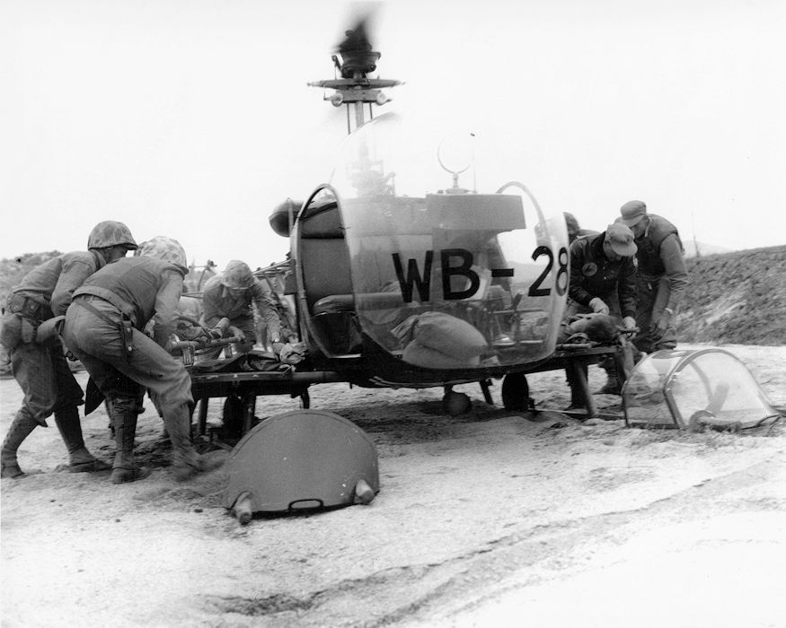 Marines and Hospital Corpsmen wearing the newly designed armored utility jacket attend to casualties in Korea, 1952. The jacket was designed by the Naval Medical Field Research Laboratory (NMFRL) in Camp Lejeune, North Carolina. (Photo courtesy of U.S. Navy Bureau of Medicine and Surgery's Archives)