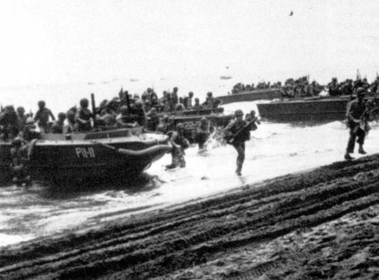 A faded image of Marines landing on Guadalcanal on August 7, 1942. The Marines landing on Guadalcanal far outnumbered the unprepared Japanese troops and civilian airfield workers on the island, so the enemy fled for the cover of Guadalcanal's jungle interior. (U.S. Navy courtesy photo)