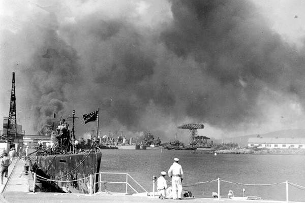 The view of the Pearl Harbor Navy Yard from the Submarine Base during the Dec. 7, 1941, attack. The USS Narwhal is in the left foreground. In the distance are several cruisers, with large cranes and 1010 Dock in the right center. (Official U.S. Navy Photograph)