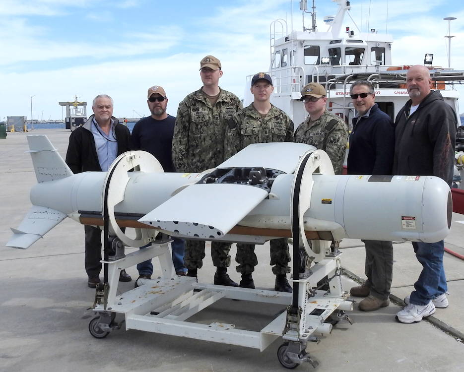 March 15, 2019 - The AN/AQS-20C (Q-20C) Sonar Sensor Post Mission Analysis (PMA) Operators gather pier side with the Naval Surface Warfare Center Panama City Division (NSWC PCD) Q-20C project team's subject matter experts. Pictured from left to right are: NSWC PCD Q-20C Project Lead Joe Thomas; Technician David Barnett; PMA Operator/Mineman First Class Petty Officer Jonathan Roden; PMA Operator/Aerographer's Mate Chief Petty Officer Larry Pacquer; PMA Operator/Mineman Petty Officer Third Class Jeremy Woods; Technician Dan Lucarell; and Lead Operator Gordon Reece. (U.S. Navy photo by Dan Broadstreet)